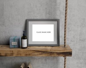 WHCC Gray Slim Frame on a wood and rope shelf with a small bottle and box.